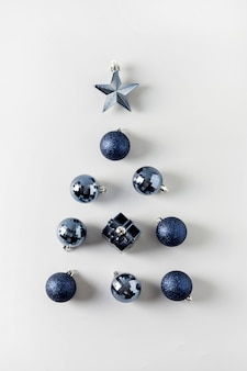 Christmas tree of classic blue balls and stars on pastel grey. close up. holiday greeting card. view from above.