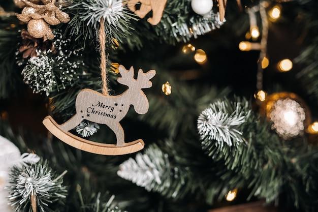 ぶら下がっている鹿と碑文のメリークリスマスとクリスマスツリーのクローズアップ。