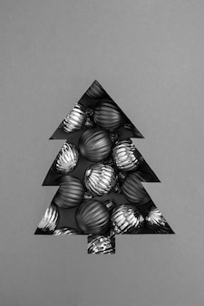 Christmas tree cut out on the gray background and filled with black balls. close-up.