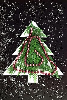 黒い壁に紙を切り取ったクリスマスツリー。緑のモミの枝を持つクリスマスツリーのシルエット。コピースペースのあるペーパーアート。