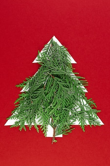 Елка вырезанная из бумаги на красном фоне. силуэт елки с зелеными еловыми ветками. карточка дизайна вырезывания бумаги рождественской елки. бумажное искусство с копией пространства.