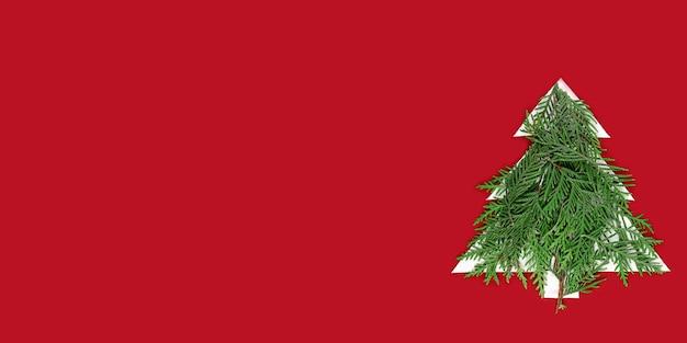 赤い壁に紙を切り取ったクリスマスツリー。緑のモミの枝を持つクリスマスツリーのシルエット。クリスマスツリー切り絵デザインカード。コピースペースのあるペーパーアート。