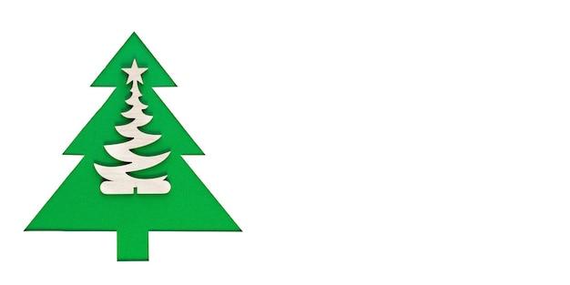 白い壁に紙から切り出されたクリスマスツリー。緑のクリスマスツリーのシルエット。クリスマスツリー切り絵デザインカード。コピースペースのあるペーパーアート。