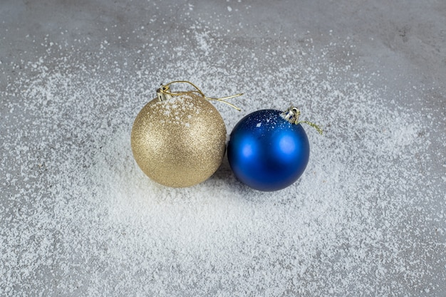 Christmas tree decor balls sitting on a pile of coconut powder on marble surface