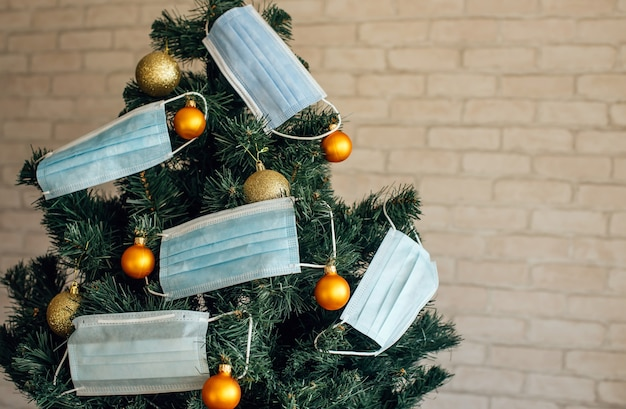 Christmas tree decorated with blue medical masks and golden balls, close up. concept of 2021 new year amid the coronavirus pandemic. symbol of holiday in quarantine. image with space for text.