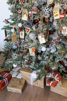Елка украшена елочными украшениями и подарками