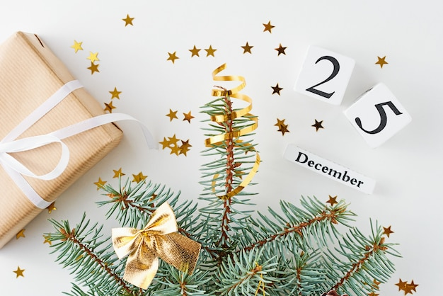 Christmas tree decorated with golden stars and gift box on white background