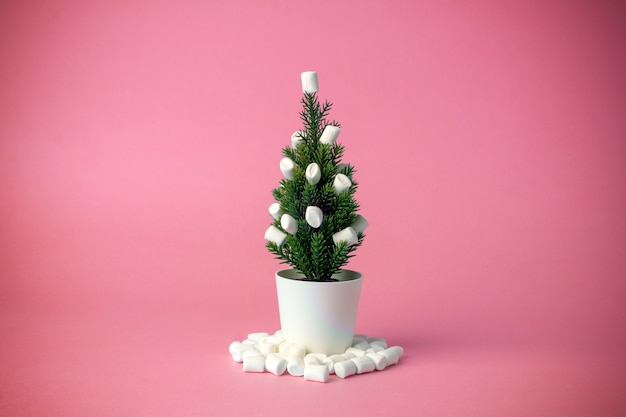 Christmas tree decorated with marshmallows instead of toys on a pink background.