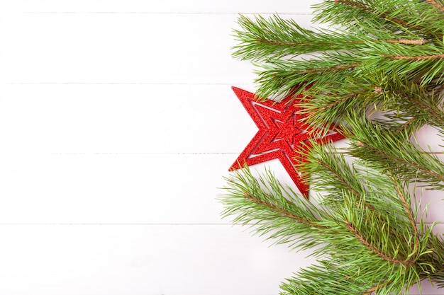 Christmas tree decorated with red star and fir branches. top view. background copyspace