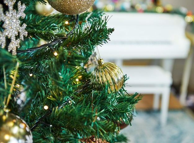 おもちゃで飾られたクリスマスツリー。白いグランドピアノの表面に対して