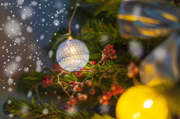 Christmas tree decorated with toys. christmas decoration in nature, bow, balls, red berries. evening snowy winter. burning colorful garland