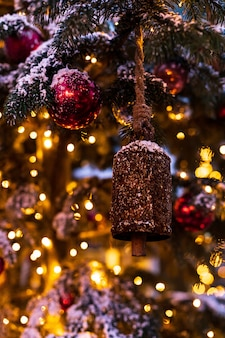 Christmas tree decorated with vintage bells and balls on a blurred abstract sparkling