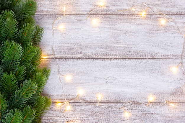 Christmas tree decorated with a yellow garland on a wooden background