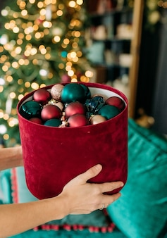 Christmas tree decoration ball gift box in woman hands