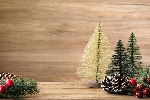 テーブルの背景にクリスマスツリーの装飾。松ぼっくり、ヤドリギ、壁に掛かっているベルボール