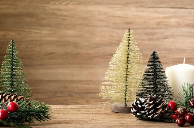 木製table.pineコーン、ヤドリギ、ベルボールにぶら下がっている壁にクリスマスツリーの装飾