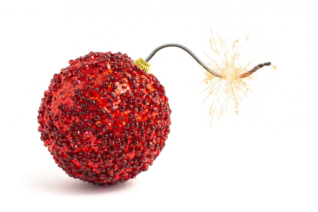 Christmas tree decoration. red bomb ready to go off with golden sparkles on white.