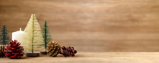Christmas tree decoration on table with snow. pine cone, mistletoe and bell ball hanging with wall