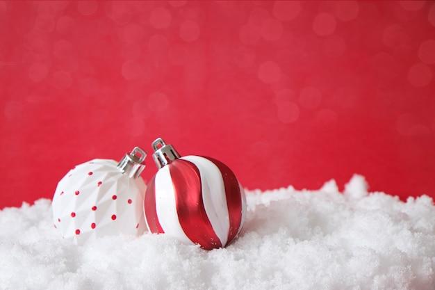 Елочные украшения, белые и красные шары, на снегу. рождественская открытка, макет