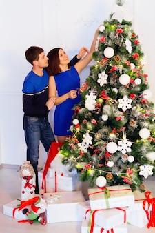 クリスマスツリーの装飾。若いカップルが一緒に緑の木にクリスマスボールを置く