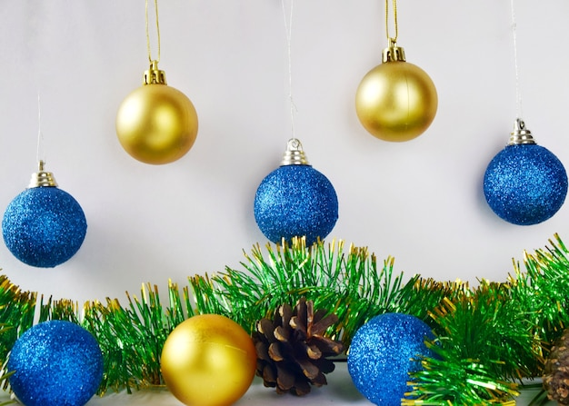 Christmas tree decorations blue and yellow balls on white wall with tinsel and cones close up.