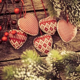 木製の背景の枝にぶら下がっているクリスマスツリーの装飾冬の休日