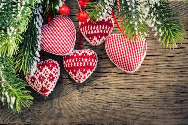木製の背景に枝にぶら下がっているクリスマスツリーの装飾。冬の休日の概念