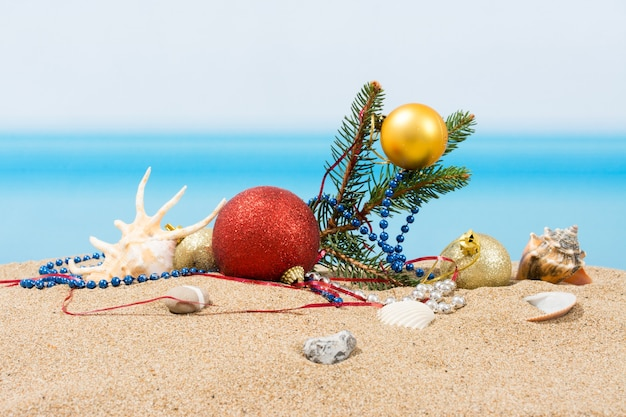 Елочные украшения на пляже в тропиках. концепция новогоднего праздника в жарких странах Premium Фотографии