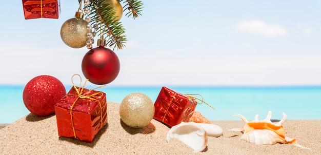 열 대 바다에서 해변에 크리스마스 트리 장식. 뜨거운 나라에서 새해 휴가의 개념
