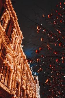 モスクワの赤の広場の通りに赤いクリスマスボールとクリスマスツリーのお祝いの輝く枝