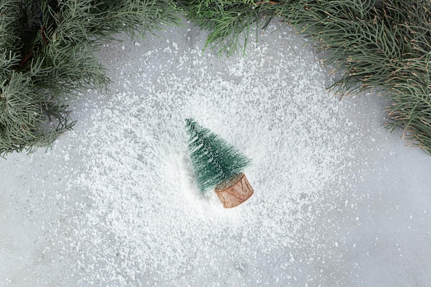 Christmas tree figurine next to an evergreen tree branch on marble table.
