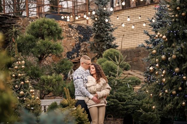 Рождественская елка еловые ветки. молодая пара украшает елку снаружи. рождественские украшения, леденцы и шары.