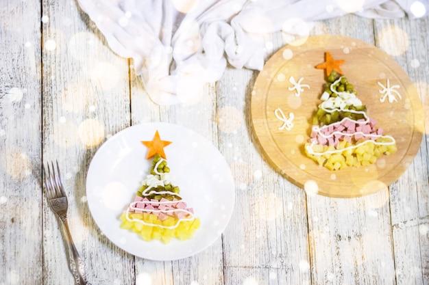 Рождественская елка из салата оливье в тарелке на белом деревянном столе. вид сверху с копией пространства. тонированное боке и снег