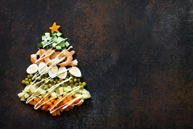 茶色のさびた石または金属の背景にサラダオリビエからのクリスマスツリー上面図