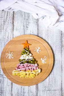 Новогодняя елка из салата оливье на разделочной доске на белом деревянном столе. вид сверху с копией пространства.