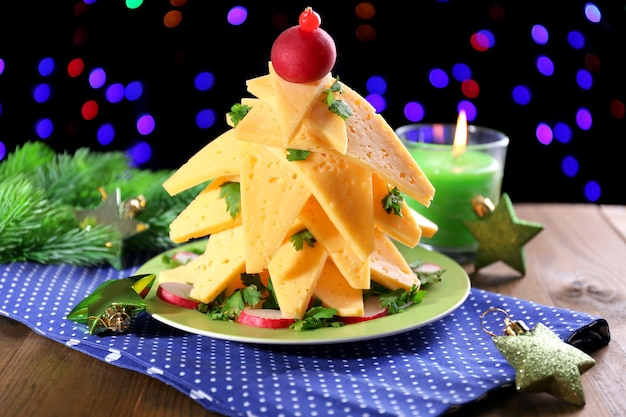 Christmas tree from cheese on table on dark