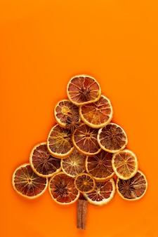 Christmas tree from dry oranges on orange background.