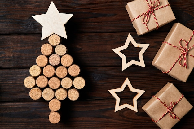 Christmas tree from wine corks with a star on top and gift boxes, stars on a wooden background
