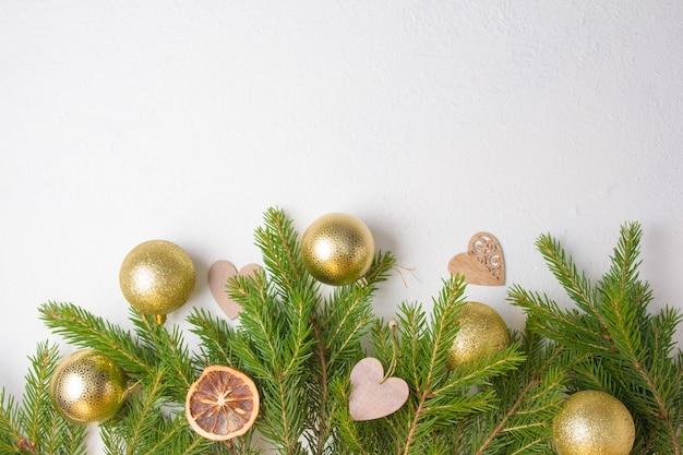Елочные золотые шары и натуральные еловые ветки на белом фоне, вид сверху, самодельные экологически чистые елочные игрушки на свежих еловых ветках
