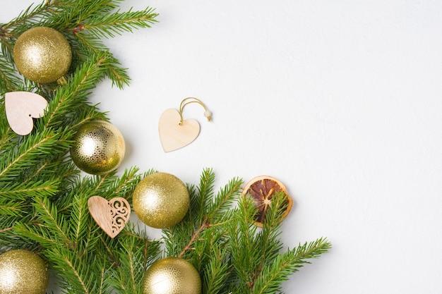 Елочные золотые шары и натуральные еловые ветки на белом фоне, вид сверху, деревянные экологически чистые елочные игрушки на свежих еловых ветках