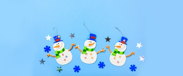 飾りをぶら下げてクリスマスツリー。青い背景に雪だるまのパーツ。
