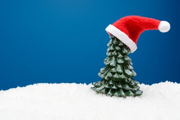 눈 속에서 크리스마스 트리 모자 산타 클로스