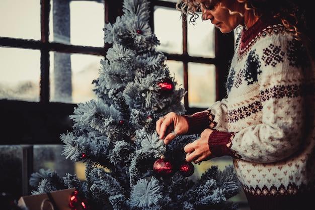 幸せな女性と一緒に家でクリスマスツリーの休日の装飾