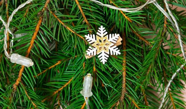 Елка праздник украшение деревянная снежинка на елке с новогодними гирляндами