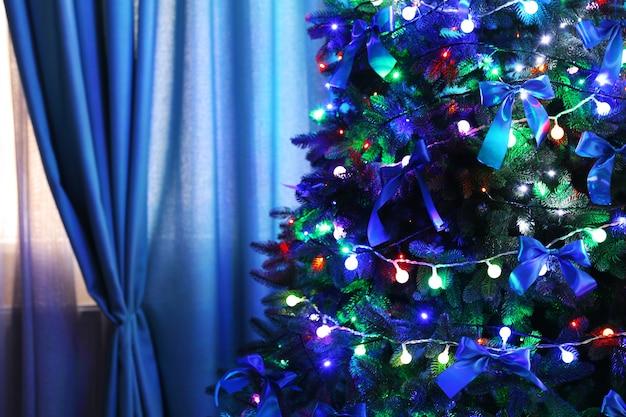 Рождественская елка в комнате на фоне окна