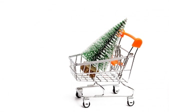 Christmas tree in a supermarket trolley on an isolated white background.