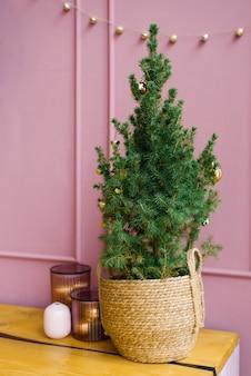 분홍색 벽을 가진 부엌에있는 고리 버들 세공 바구니에 크리스마스 트리