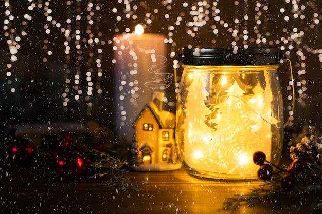 Рождественская елка в стеклянной банке, блестящие домашние шары, конус и свеча на блеске с фоном снежинок