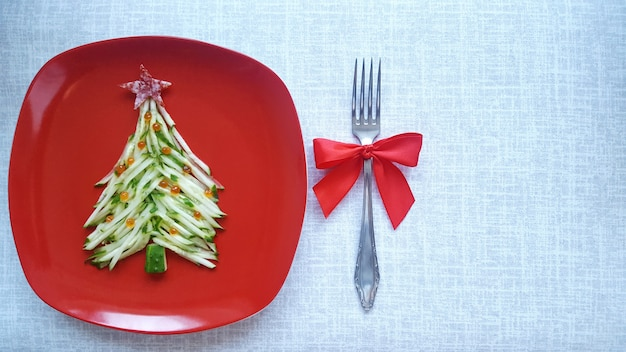 Christmas tree is made of sliced cucumber and decorated with red caviar. new year's design of dishes.