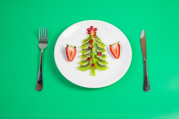 Christmas tree of kiwi and pomegranate with fork and knife
